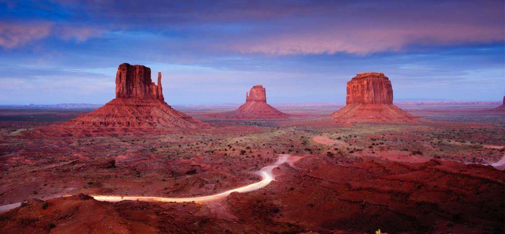 Auta projíždějící Monument Valley